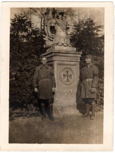 World War One (WWI): Two soldiers standing by a monument with a large iron cross on it