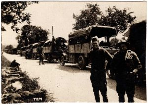 World War One (WWI): Soldiers standing on road in front of long line of transport vehicles.